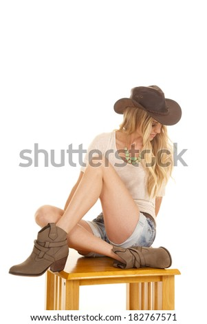 a cowgirl in her hat and boots sitting on a wooden table looking down. - stock photo