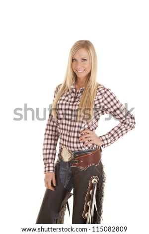 A cowgirl in her plaid shirt and chaps with  a smile on her face. - stock photo