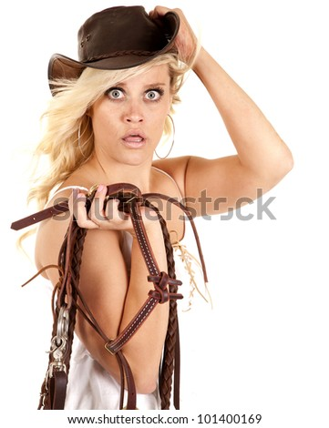 A cowgirl is holding a bridle and her hat and looks surprised. - stock photo
