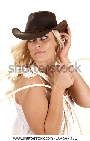 A cowgirl is holding a rope over her shoulder and looking back. - stock photo