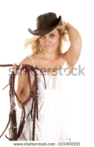 A cowgirl is holding her hat with one hand and a bridle with the other and smiling. - stock photo