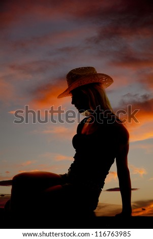 A cowgirl is sitting in the sunset as a silhouette. - stock photo