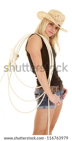 A cowgirl is standing with a rope on her shoulder looking.