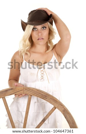 A cowgirl is standing with a wagon wheel. - stock photo