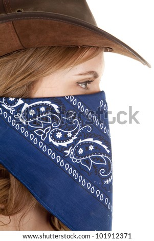 A cowgirl is wearing a bandanna and looking sideways. - stock photo