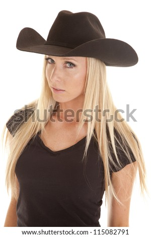 A cowgirl looking at the camera with her black hat and black shirt on with a serious expression on her face, - stock photo