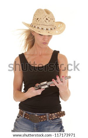 A cowgirl looking down at her gun with a serious expression.