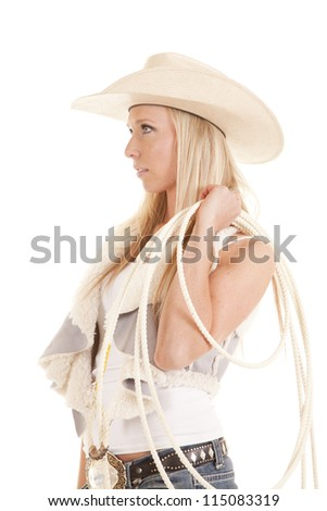 A cowgirl looking off to the side holding on to her rope. - stock photo