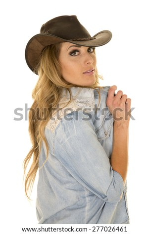 A cowgirl looking over her shoulder holding out her collar on her shirt. - stock photo