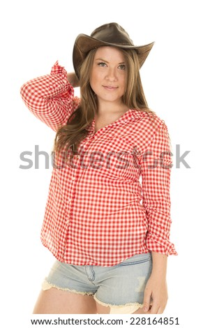 A cowgirl looking wearing her hat, in her plaid shirt. - stock photo