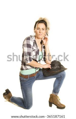 a cowgirl on her knee with her hat on her knee with a funny expression on her face.