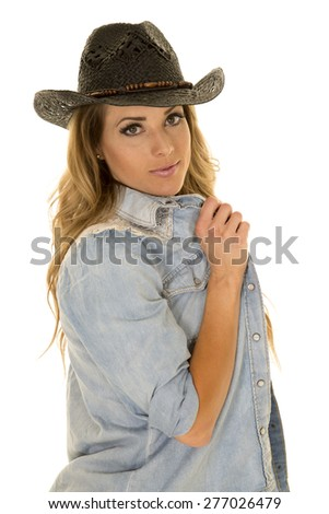 A cowgirl playing with her shirt, wearing her western hat.