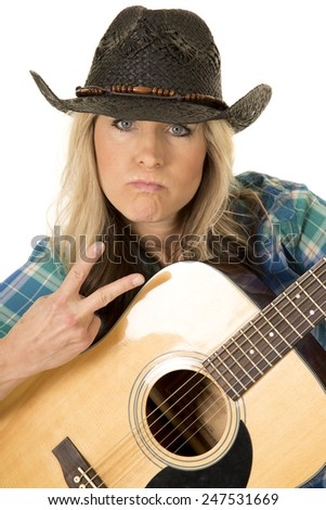 a cowgirl showing some attitude holding onto her guitar holding up the peace sign. - stock photo