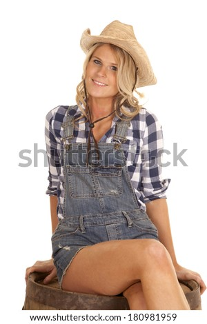 A cowgirl sitting on top of a barrel with a smile on her face.
