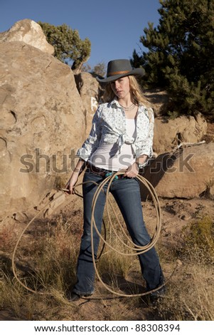 A cowgirl standing and holding on to her rope in the outdoors with a serious expression on her face. - stock photo