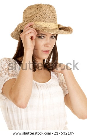 A cowgirl touching the brim of her hat looking. - stock photo