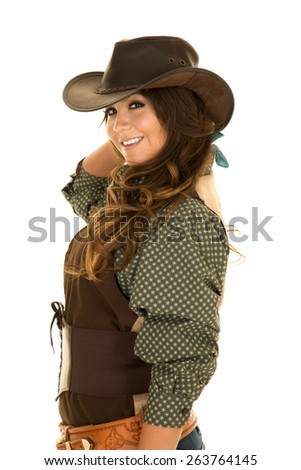 A cowgirl with a big smile on her face, looking to the side in her cowgirl hat, and her holster on.