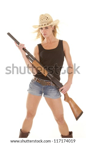 A cowgirl with a serious expression holding on to her rifle. - stock photo