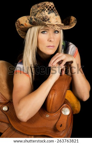a cowgirl with a serious expression on her face, leaning on her saddle. - stock photo