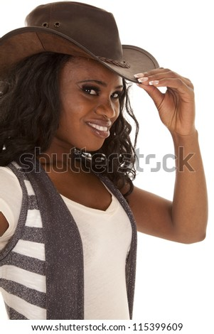 A cowgirl with a smile on her face looking at the camera and holding on to the brim of her hat. - stock photo