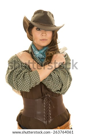 a cowgirl with her arms wrapped around herself, with her pistol on her shoulder. - stock photo