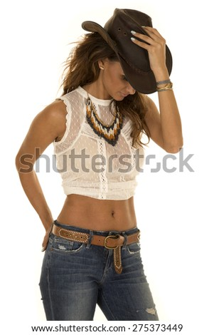 A cowgirl with her hand on her hat looking down. - stock photo