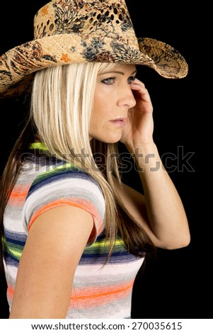 A cowgirl with her western hat looking to the side with a serious expression on her face. - stock photo