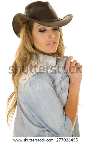 a cowgirl with her western hat on , playing with her shirt. - stock photo