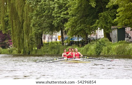 A coxed four on a canal at full speed - stock photo