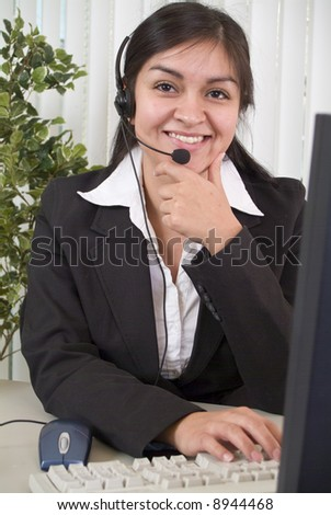 A coy or shy young woman manning a helpdesk wearing a headset. - stock photo