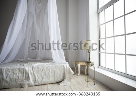 a cozy bedroom in pastel colors with a wooden floor a large fourposter