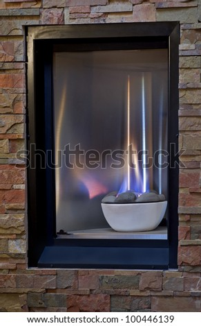 A cozy gas fireplace with blue and yellow flames set into a warm, flagstone wall. - stock photo
