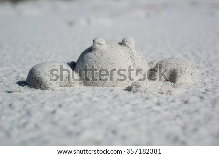 A crab made out of sand sits on a sandy beach