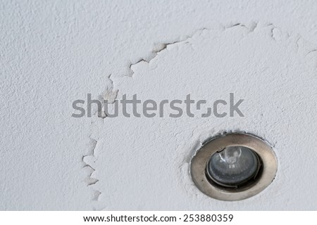 A cracked ceiling with peeling layer due to water leak. LED light.  - stock photo