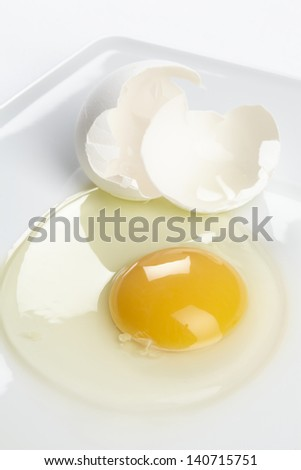 A cracked hen�´s egg with eggshell on a white china plate.