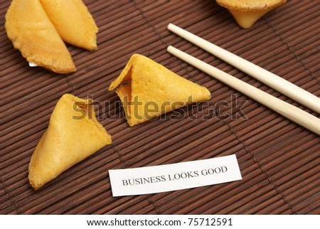 A cracked open fortune cookie stating that business looks good. - stock photo