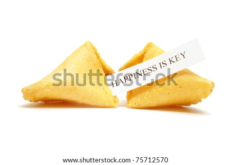 A cracked open fortune cookie stating that happiness is key. - stock photo