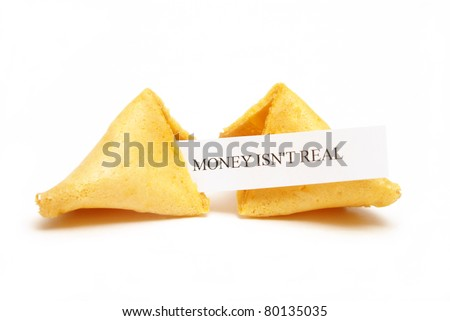 A cracked open fortune cookie stating that money isn't real. - stock photo