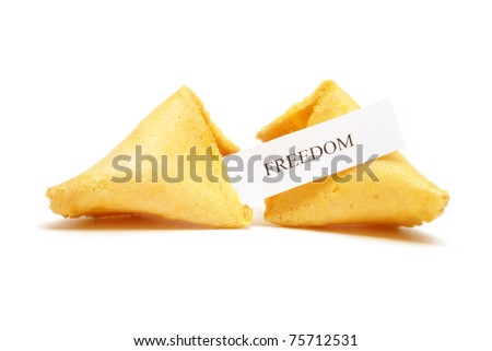 A cracked open fortune cookie stating the word freedom. - stock photo
