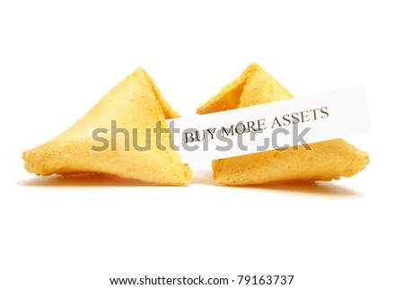 A cracked open fortune cookie stating to buy more assets. - stock photo