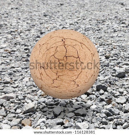 A cracking brown mud ball levitating above a granite rubble landscape for the concept of an apocalyptic future earth. - stock photo