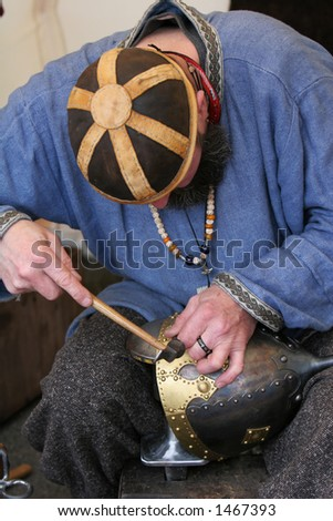 A craftsman chiseling inscription into a medieval soldiers helmet - stock photo