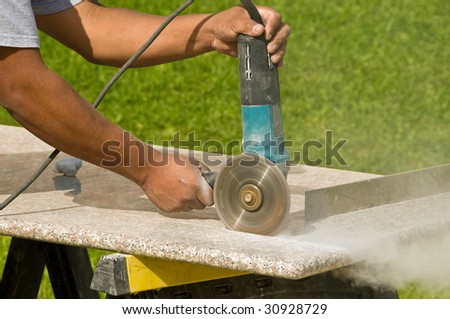 A craftsman cuts granite countertops on a kitchen remodel - stock photo