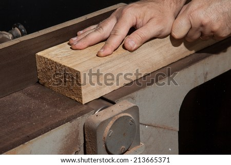 A craftsman flattening a wooden plank in electric table planer