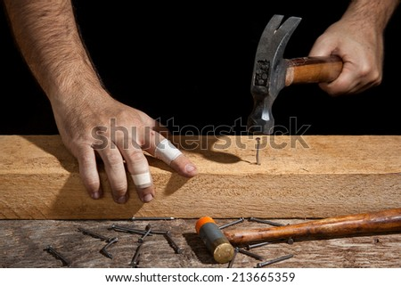 A craftsman hammering bent nail with difficulty - stock photo