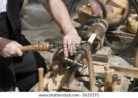 A craftsman turning wood on a lathe - stock photo