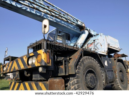"""A crane mounted on an undercarriage with four rubber tires for off-road and """"rough terrain"""" applications. - stock photo"""