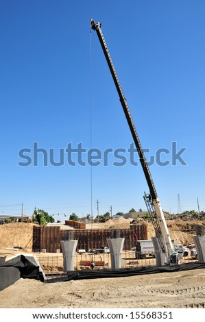 A crane with long boom helps construct a major freeway interchange, California - stock photo