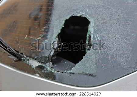 a crashed car heated rear window broken by an accidentally cast stone - stock photo