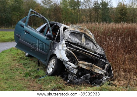A crashed, wrecked and burnt out car. - stock photo